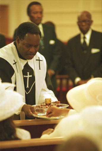 Reverend Eugene Lumpkin, Jr., Pastor of San Francisco's Ebenezer Baptist Church, shares libations during the close of Sunday ceremonies, March, 2002.