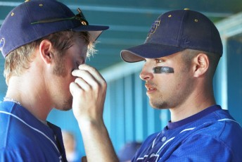SF State outfielder Tanner Herrick (left) gets assistance with his 'warpaint' from teammate Stefan McGovern before a game at Sonoma State, April 1, 2002.