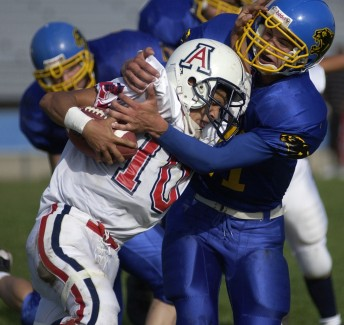 Prospect High's Garrett Karren tries to wrestle the ball from the American Eagles Peter Alvear during a game at Prospect High School Sept. 27, 2002.  The Panthers lost to the Americans 20-7.