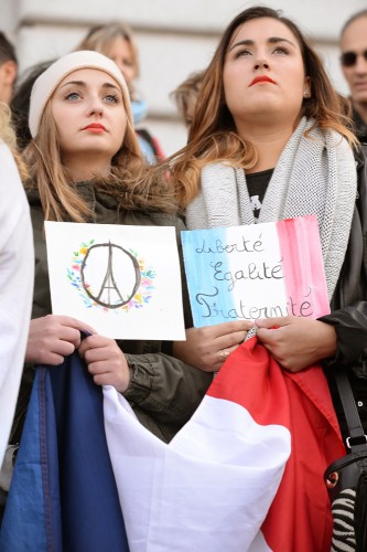 Anais Gazeau of Troyes and Marion Bertranet of Bordeaux - both in the United States to work as nannies - came to show their support for France and honor the memories of the more than one hundred killed in Friday's terrorist attacks in Paris outside of San Francisco's City Hall, November 15, 2015. Photo by Stephen Dorian Miner